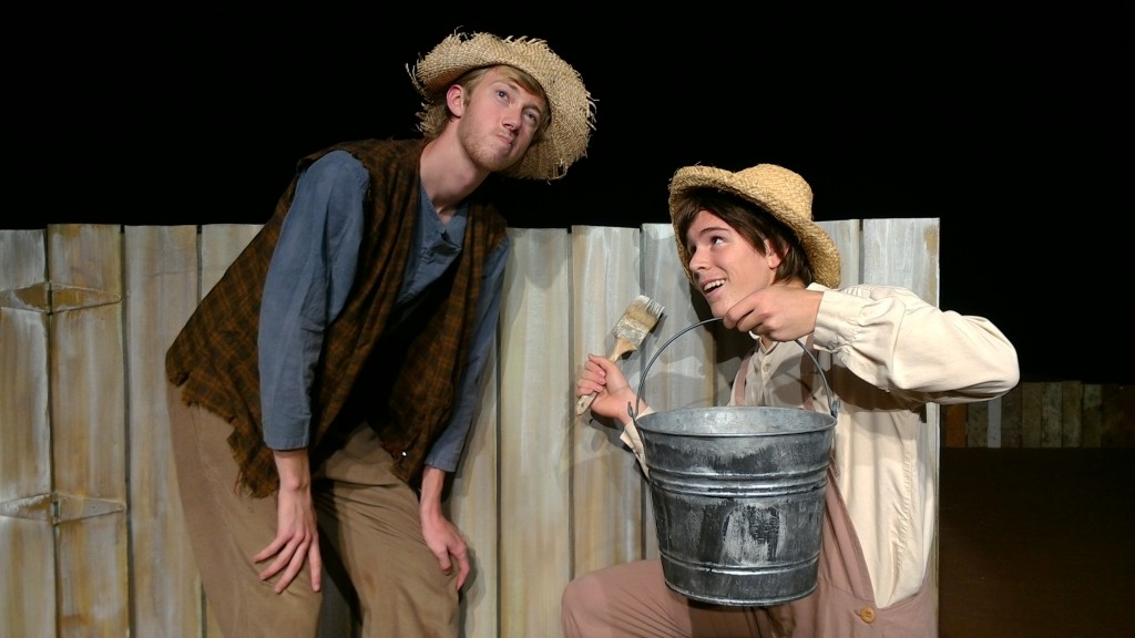 Tom Sawyer (William Van Nes) tries to persuade Huck Finn (Elijah Morgan) to help him paint the fence in ARIEL Theatrical's production of The Adventures of Tom Sawyer playing August 5, 6, 12,13, 19, & 20 at the Karen Wilson Children's Theatre in Salinas. photo credit: Stephen Massott